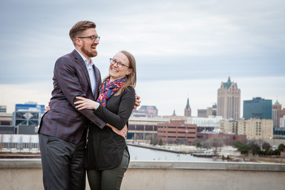 Engaged couple laughing in front of Milwaukee Skyline